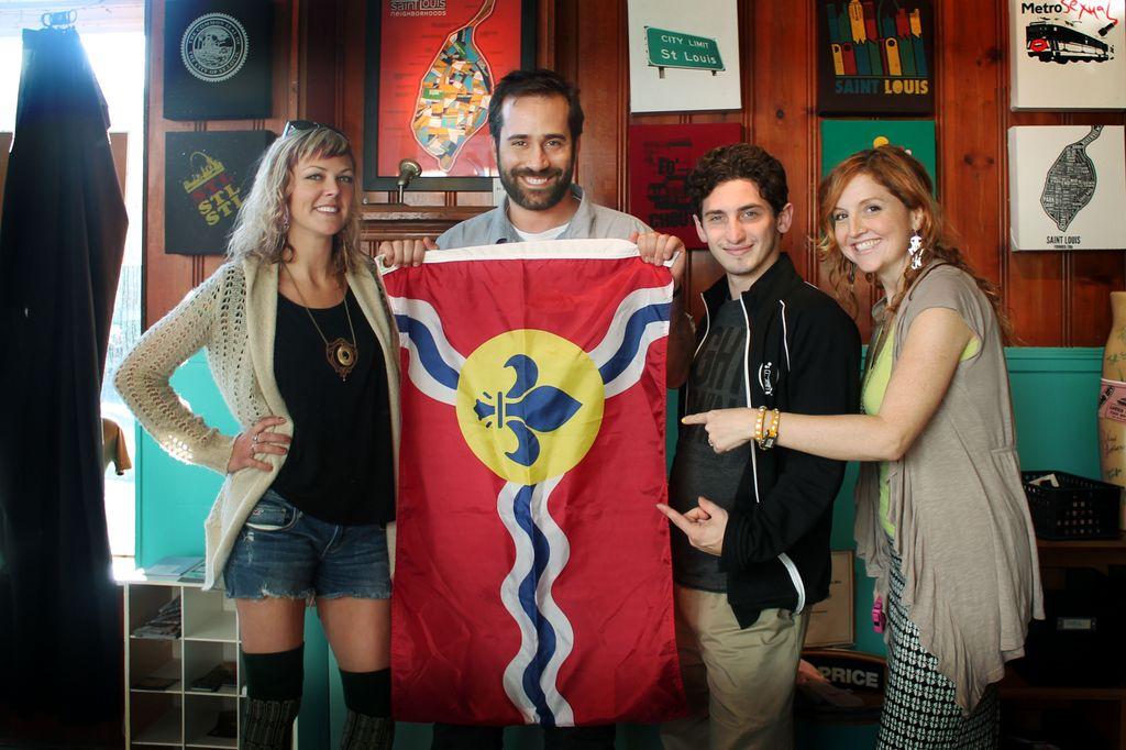 Scarlett Garnet, GM of Reddit Erik Martin and Startup Weekend Zach Cohen holding up the St. Louis flag in STL Style House